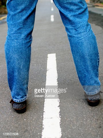 Womans legs in the middle of the road : Stock Photo