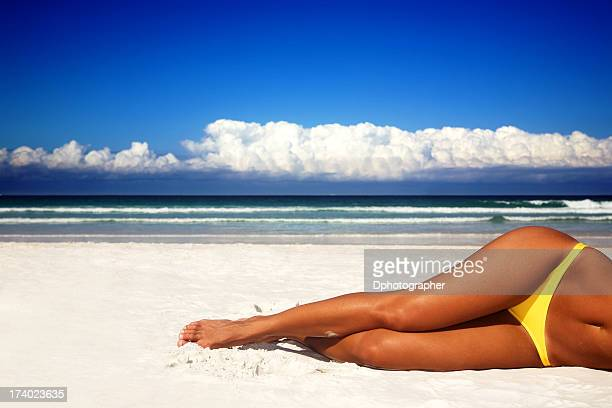 Woman's legs lying on a sandy beach on a bright sunny day