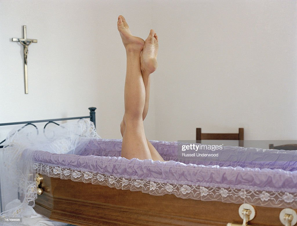 A woman's legs raising out of an open coffin