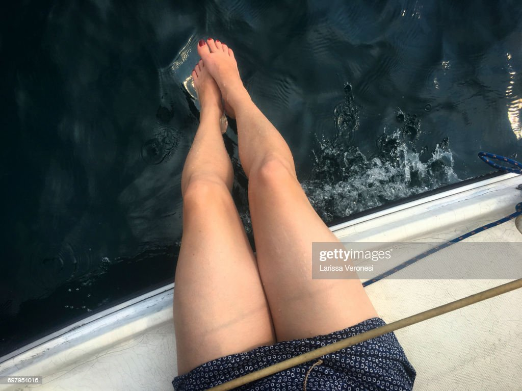 woman's legs sitting on the deck on a sailboat, Lake Garda, Italy : Stock-Foto