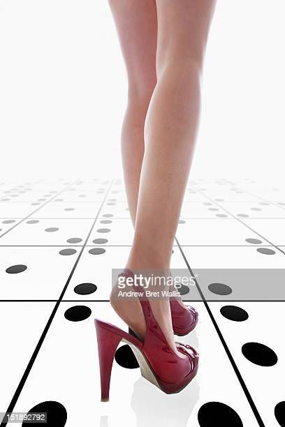 A woman's legs stepping across dice tiles
