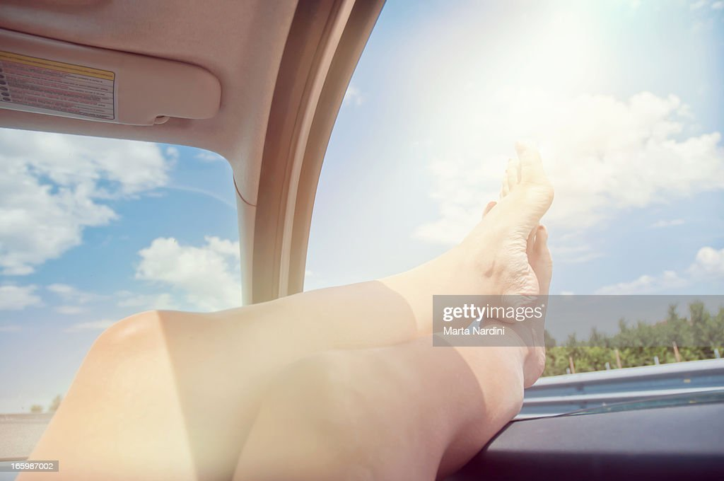 Woman's legs, sticking out of car window