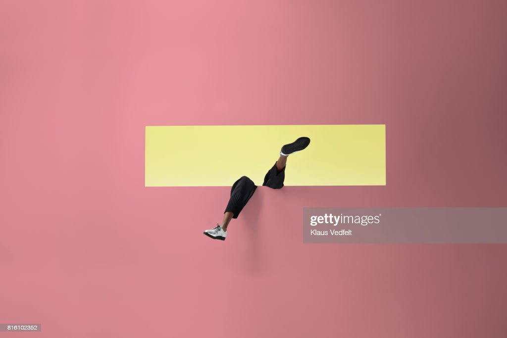 Womans legs sticking out of rectangular opening in coloured wall and looking up : Stock Photo