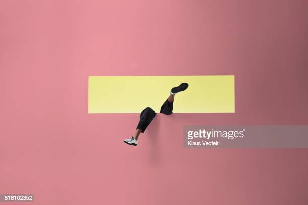 Womans legs sticking out of rectangular opening in coloured wall and looking up