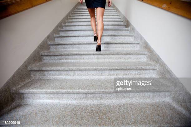 Womans legs walking up a flight of stairs
