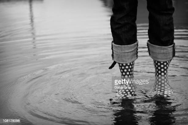 Woman's Legs Wearing Rainboots in Giant Puddle, Black and White