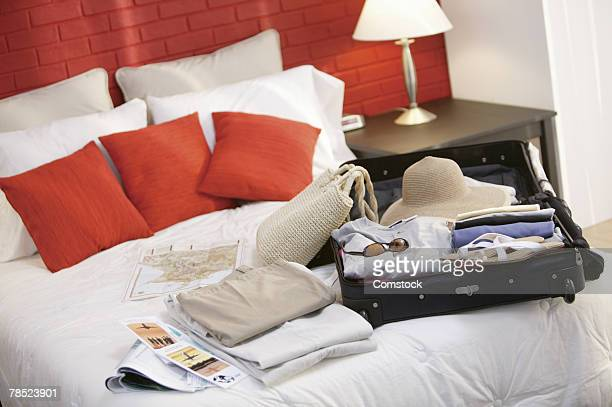 Woman's luggage and travel brochures on bed