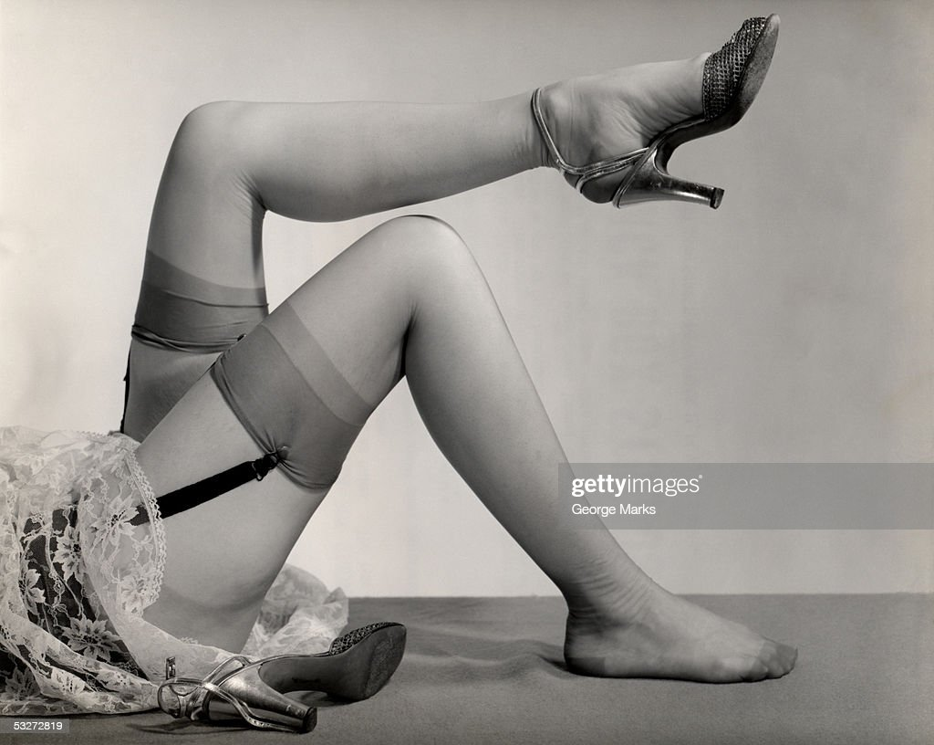 Woman's nylon stocking legs with garters and heels : Stock Photo