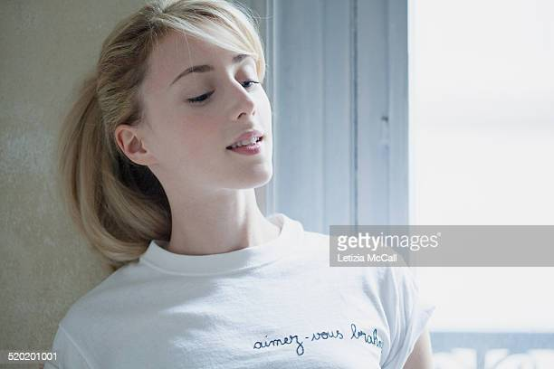 Woman's portrait at window with a white t-shirt
