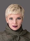 Beautiful woman with short hair blonde wearing khaki scarf on grey background. Close-up portrait. Model shot. Fashion  hairstyle with fringe, haircut and makeup in grey shades. Lilac lips. Modern high
