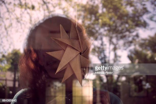 Woman's reflection in window with origami ornament; both interior and outside visible