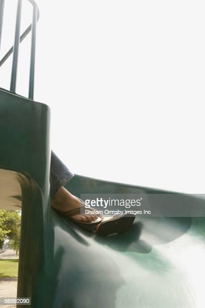 Woman's sandaled feet resting on children's slide