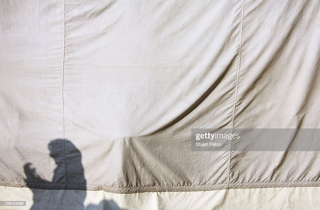 Woman's shadow on tent canvas : Stock Photo