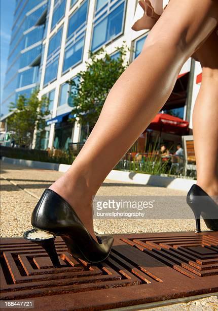 Woman's shoe trapped in sidewalk grate