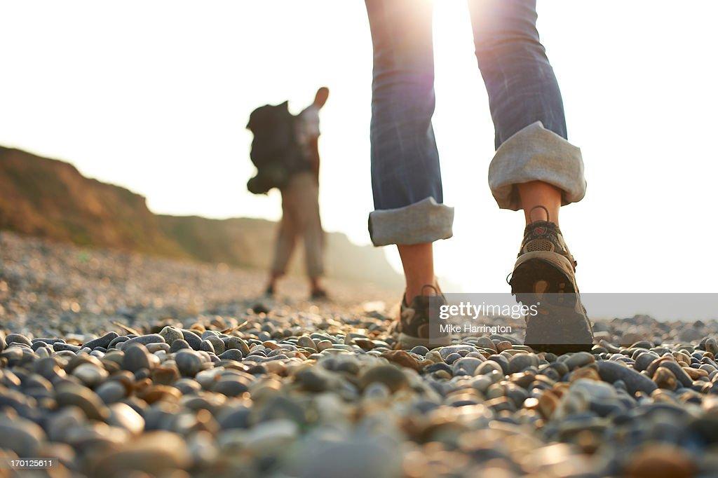 Woman's shoes as she walks along pebble beach.