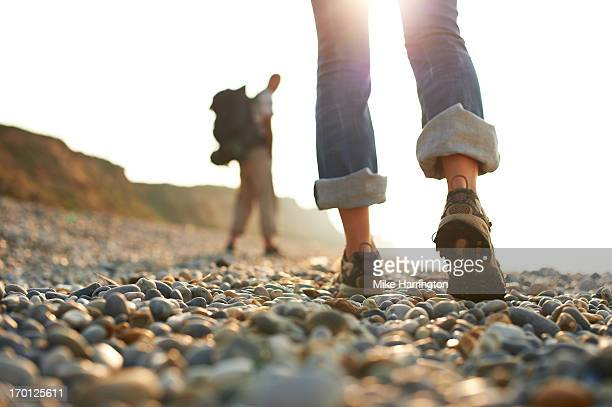 Woman's shoes as she walks along pebble beach.