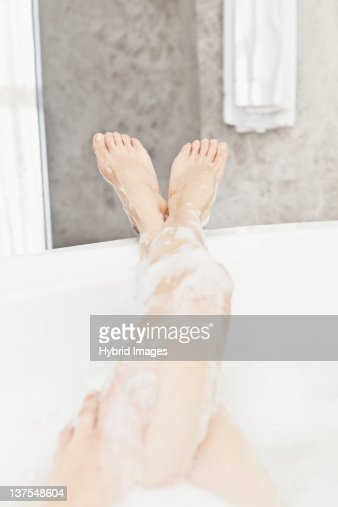 Womans soapy legs in bubble bath : Stock Photo