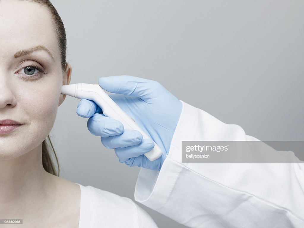 Woman's Temperature Being Taken By Ear.