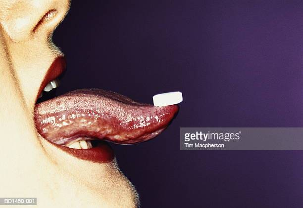 Woman's tongue with white tablet balancing on tip, profile, close-up