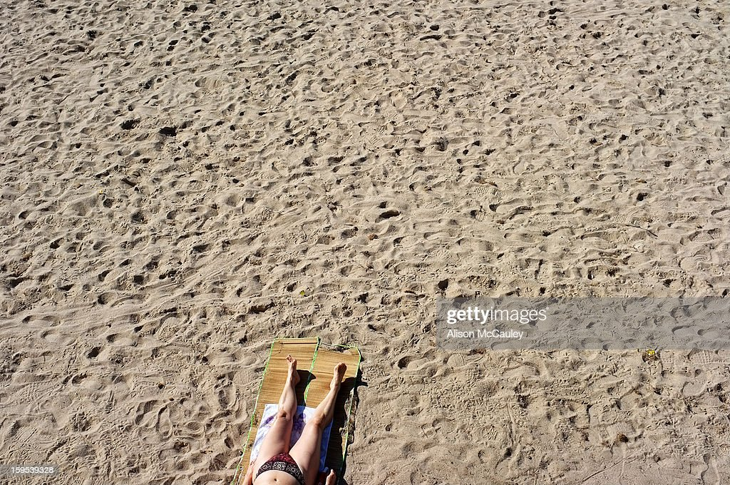 CONTENT] A woman's torso and legs can be seen from above. She is in her bikini, sunbathing on a beach in Cannes. She's the only one on this stretch of beach and she's surrounded by nothing but trampled sand.
