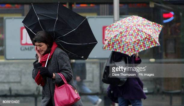A woman's umbrella is blown inside out as strong winds and rain hit Manchester city centre