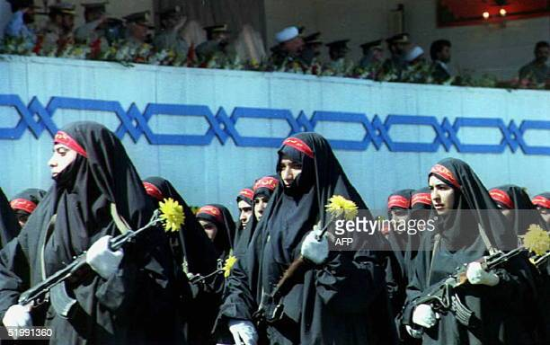 A woman's unit of the Bassidji or the Islamic volunteer militia parades in front of Iranian President Ali Akbar AchemiRafsandjani and Iranian armed...