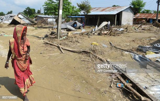 A womans walks past an area damaged by flood in Itahari Sunsari district some 250 kms from Nepal's capital Kathmandu on August 16 2017 At least 221...