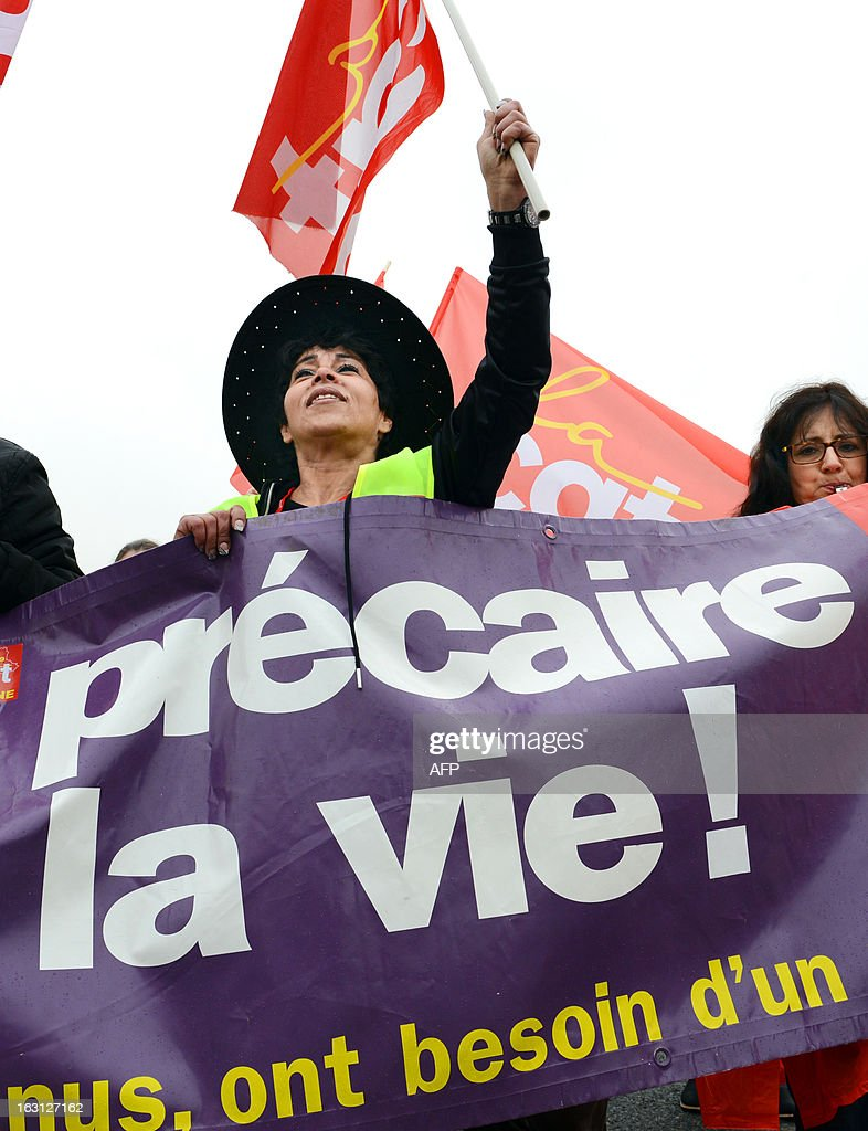 A womans waves a CGT trade unions flagon on March 5, 2013 in Lyon, southeastern France, during a demonstration called by CGT and fellow union FO to protest against last January 11's interbranch agreements between several workers' unions and the French employers' association Medef, on employment's safeguard. The government will discuss the agreement in the March 6 cabinet meeting.