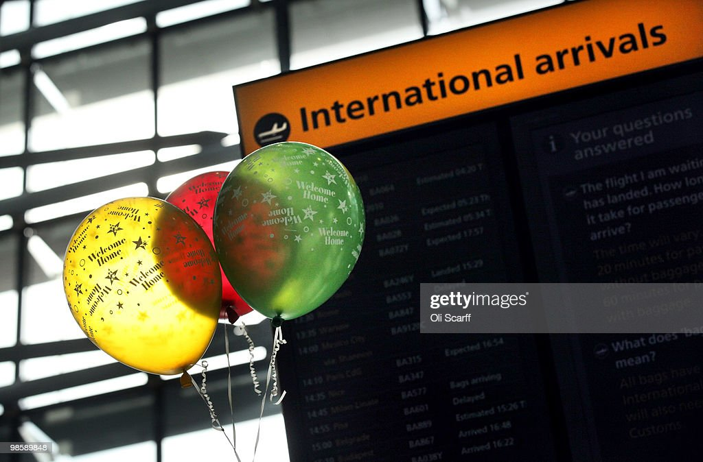 A woman's 'Welcome Home' balloons are seen in front of a flight information board as she waits in the arrivals lounge of Heathrow airport's Terminal 5 on April 21, 2010 in London, England. Airlines are beginning to resume a normal service following six days of airport closures due to volcanic ash from Iceland covering British airspace.