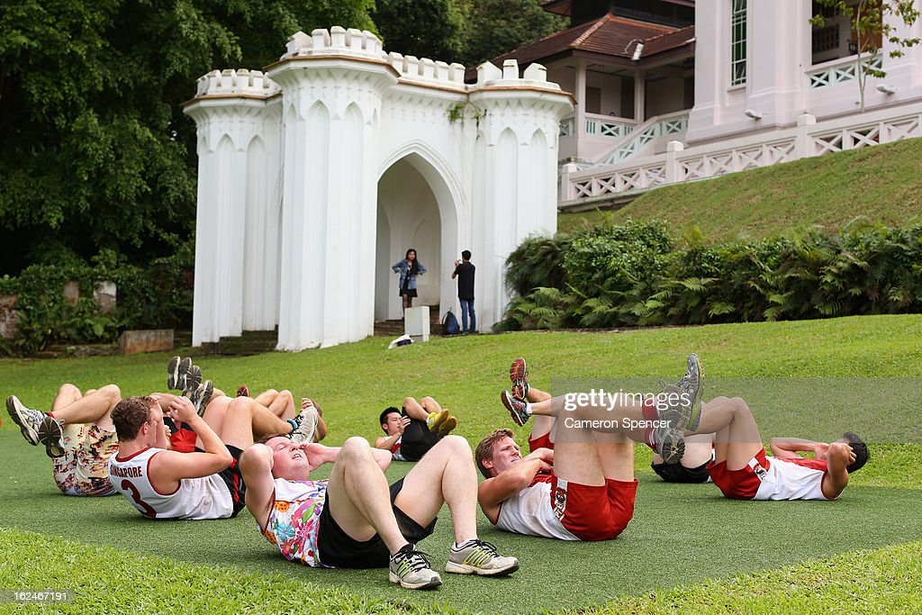Wombats players perform sit-ups in front of the Fort Canning Centre during a Singapore Wombats Aussie Rules training session at Fort Canning Park on February 23, 2013 in Singapore. The Singapore Australian Football Club (SAFC), known as the Singapore Wombats is celebrating 20 years this year. Established by Australian expatriates in 1993, the amateur team plays clubs from Indonesia, Japan, the Philippines, Thailand and Vietnam in an Asian Championship.