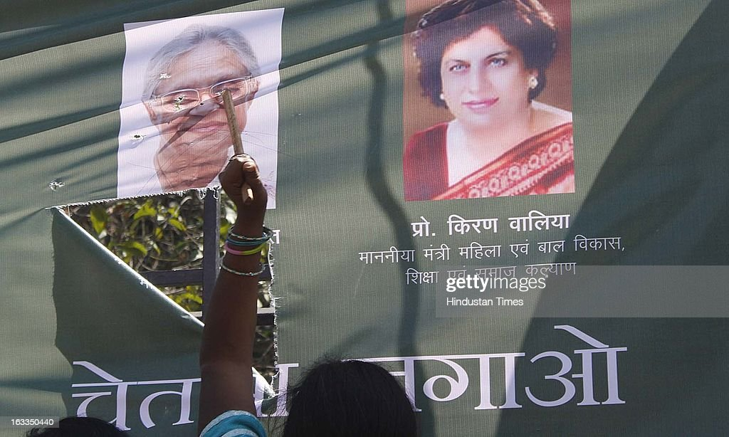 BJP women activists tearing the hoarding of Delhi Chief Minister Sheila Dikshit as they protest against lack of safety for women in the city during a function oraganized at Talkatora stadium on the occasion of International Women's Day on March 8, 2013 in New Delhi, India. Sheila Dikshit was Chief guest of the event.