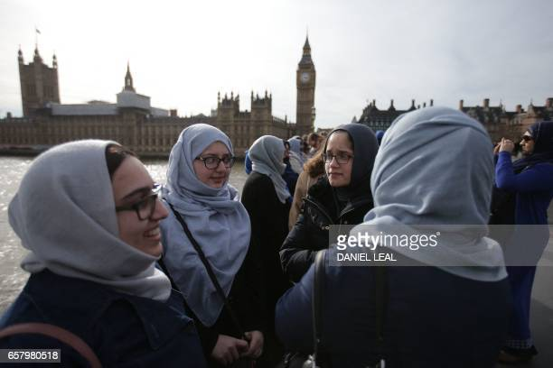 Women activists wearing blue gather to hold hands on Westminster Bridge in front of the Houses of Parliament to honour the victims of the March 22...