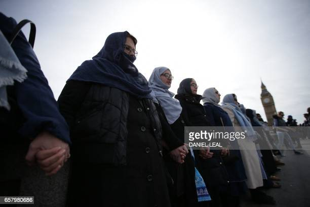 Women activists wearing blue hold hands on Westminster Bridge in front of the Houses of Parliament to honour the victims of the March 22 attack in...
