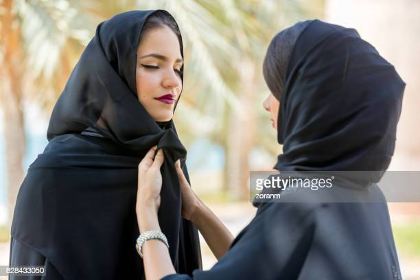 Women adjusting hijab to each other