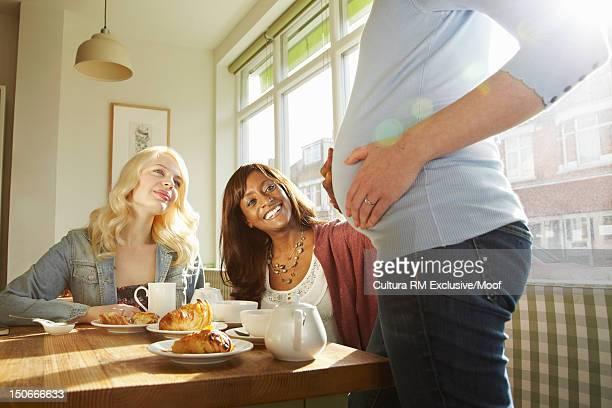 Women admiring friends pregnant belly