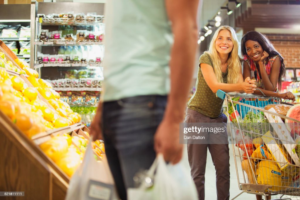 Women admiring man shopping in grocery store
