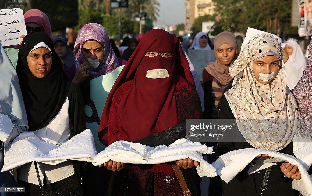 Women amongst the demonstrators in Al-Nahda Square of Giza carry cerements as a remembrance of those who lost their lives during the interventions of the Egyptian security forces on August 1, 2013 in Cairo, Egypt. Following the ousting of Egypts first democratically elected president Mohammed Morsi by the military, supporters associated to the Muslim Brotherhood started a series of protests in various cities of the country.