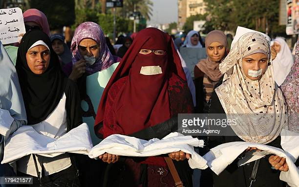 Women amongst the demonstrators in AlNahda Square of Giza carry cerements as a remembrance of those who lost their lives during the interventions of...