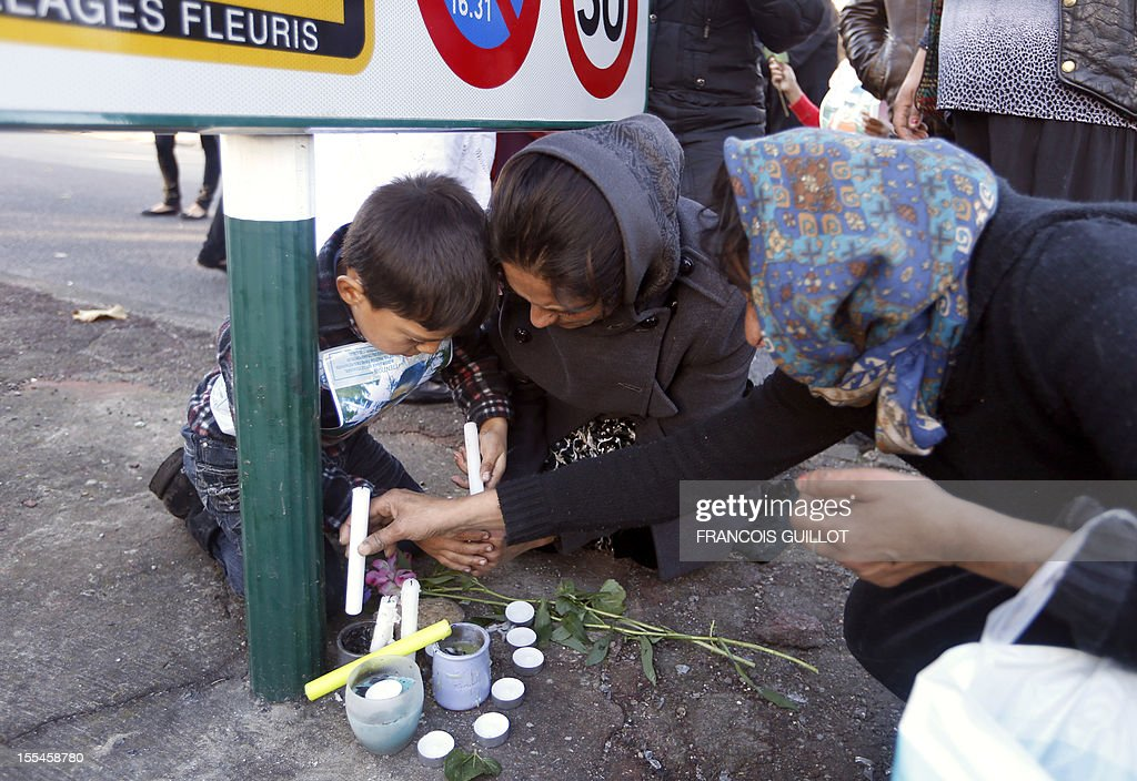Women and a boy are putting candles where two Roma teenage boys were hit by a car as they were riding on a bicycle on October 31, 2012 in Noisy-le-Grand, east of Paris, as they take part in a silent march in their memory, on November 4 in Noisy-le-Grand. One of the two boys, aged 15, died and the other one, aged 12, was seriously injured. AFP PHOTO / FRANCOIS GUILLOT