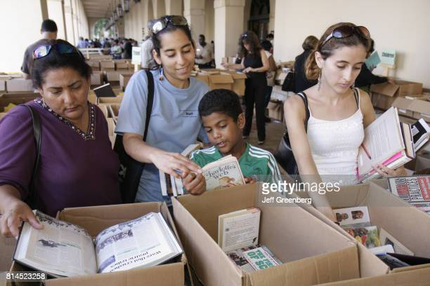 Women and a boy browsing books at the MiamiDade Public Library Book Sale