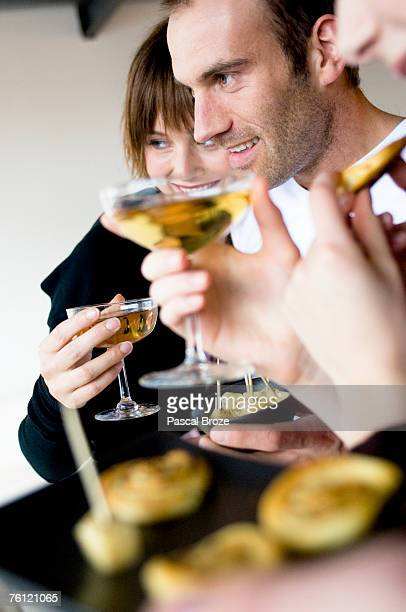 2 women and a man holding glass of champagne