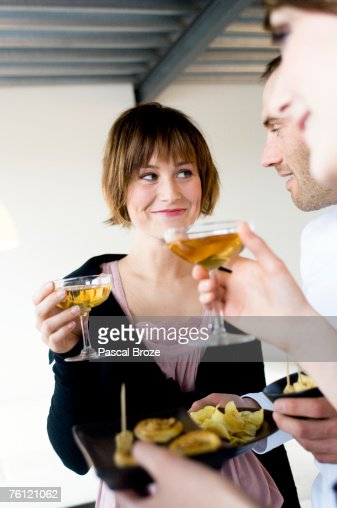 2 women and a man holding glasses of champagne