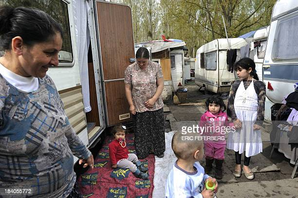 Women and children are seen near caravans on April 5 2011 in the MoulinGalant camp in CorbeilEssonnes outside Paris where about 70 Roma families live...