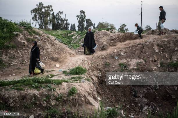 Women and children carry food given to them by Shia volunteers during fighting against Islamic State in west Mosul on April 6 2017 in Mosul Iraq...