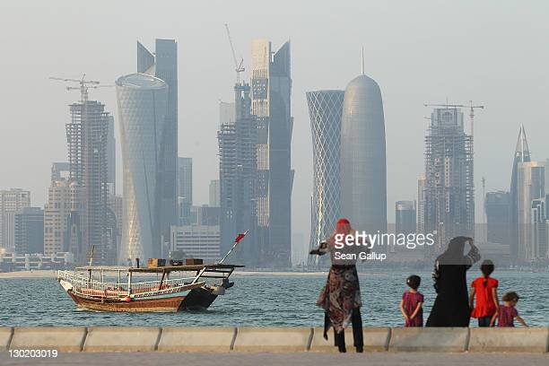 Women and children enjoy the waterfront along the Persian Gulf across from new budding financial district skyscrapers as a traditional Arab ship...