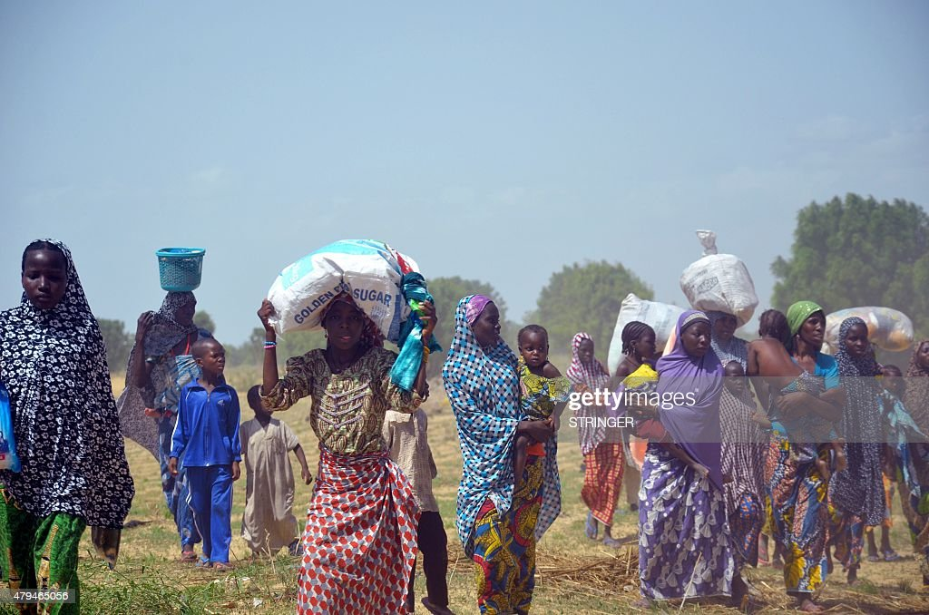 Women and children flee from home burnt by Boko Haram Islamists at Zabarmari, a fishing and farming village near Maiduguri, northeast Nigeria, on July 3, 2015. Several female suicide bombers in northeast Nigeria blew themselves up amid panicked villagers fleeing a Boko Haram attack, killing scores, the army and witnesses said on July 4. The latest carnage in series of attacks that have claimed more than 200 lives in just three days happened on Friday night in Zabarmari village, 10 kilometres (six miles) from the city of Maiduguri, the birthplace of the jihadist group. AFP PHOTO/STRINGER AFP/AFP/STRINGER/STR /PUE/MR