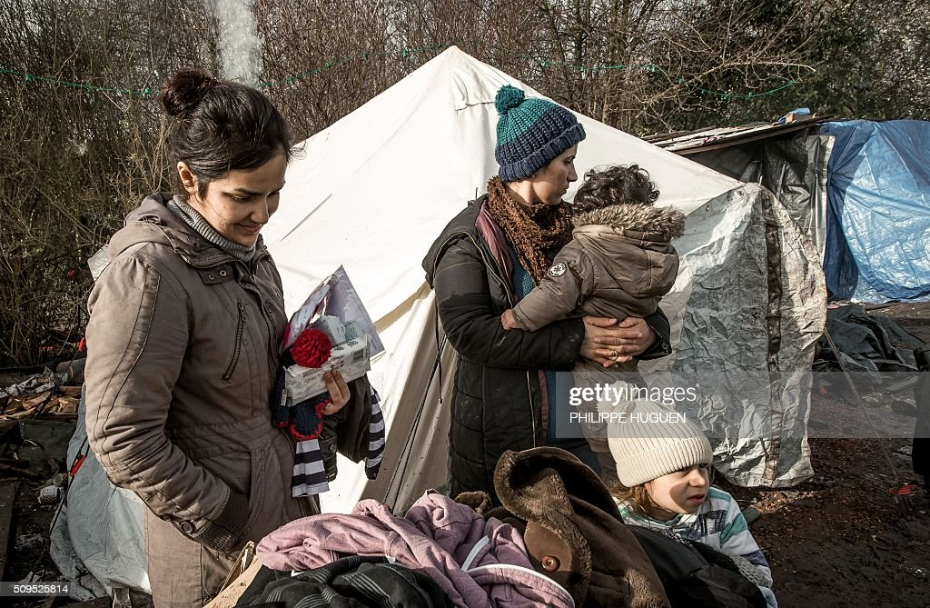 Women and children from Iraq stand in the so-called 'Jungle' migrant camp in Gande-Synthe where 2,500 refugees from Kurdistan, Iraq and Syria live on February 11, 2016 in Grande-Synthe near the city of Dunkirk, northern France. / AFP / PHILIPPE HUGUEN