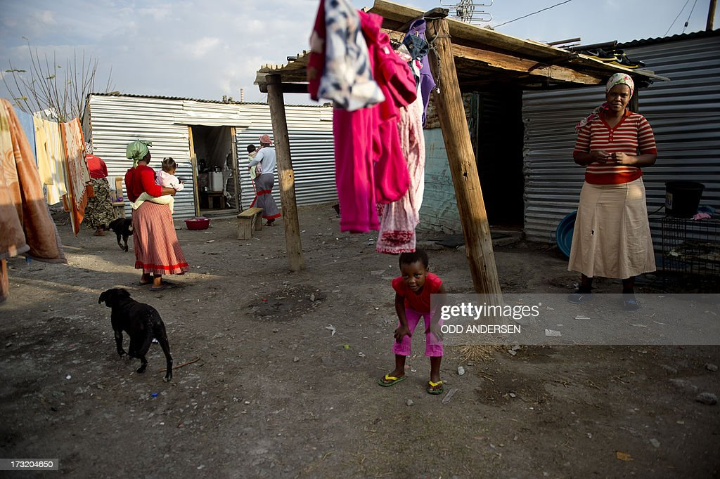 Women and children gather between shacks on July 9, 2013 in the Nkaneng shantytown next to the platinum mine, run by British company Lonmin, in Marikana. On August 16, 2012, police at the Marikana mine open fire on striking workers, killing 34 and injuring 78, during a strike was for better wages and living conditions. Miners still live in dire conditions despite a small wage increase.