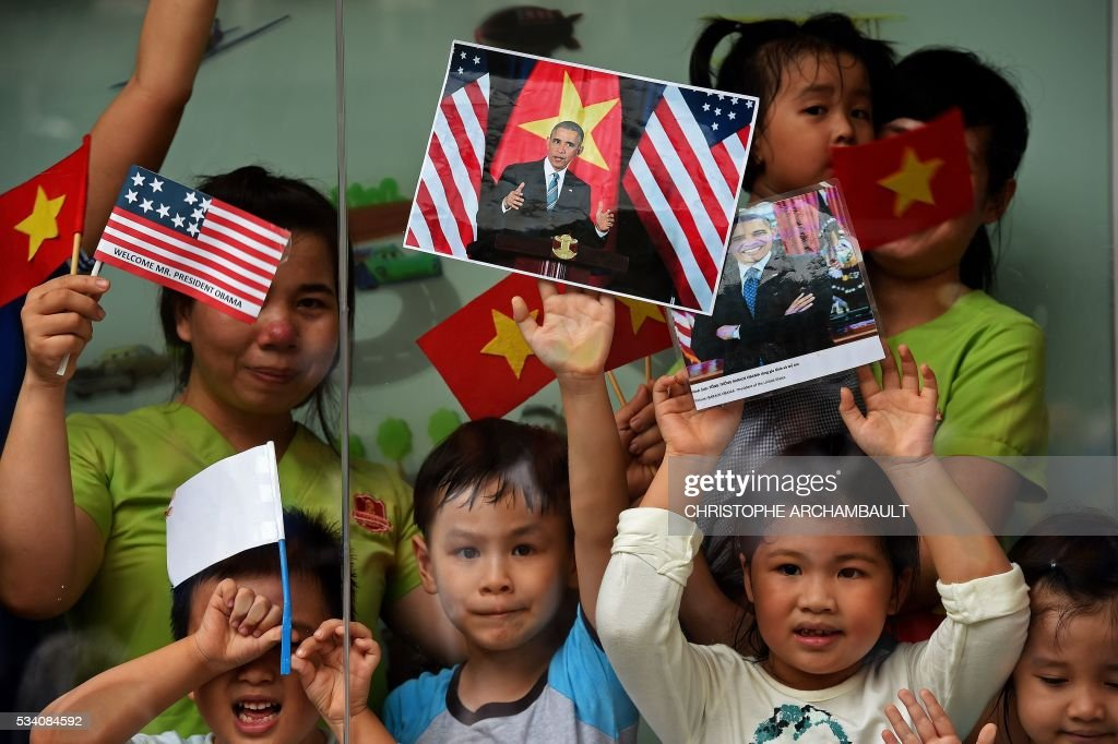 Women and children hold Vietnamese and US flags and pictures of US President Barack Obama as people line up the streets to catch a glimpse of the US leader on his way to the airport at the end of two-day visit to Ho Chi Minh City on May 25, 2016. Obama fielded questions on May 25 on everything from rap and weed smoking to leadership and his good looks at a lively town hall-style meeting with young Vietnamese, who say the US leader is a far cry from their staid Communist rulers. / AFP / CHRISTOPHE
