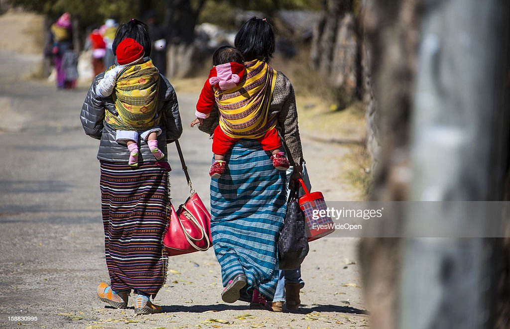 Women and children in traditional Kira dress on the way to the market or shopping near the Temple of Kurjey Lhakhang near Jakar on November 18, 2012 in Bumthang, Bhutan.
